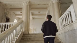 a young man climbs the old and abandoned staircase, the photographer takes photos of an abandoned mansion and explores the building with pleasure