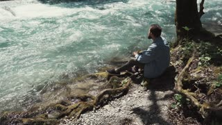 a young man is on the nature on a warm summer day, he looks at the stream of water, which makes you think about the eternal, the river is rapidly moving into the distance