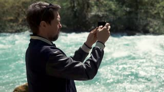 a young man takes photos on a mobile phone, holds a smartphone in his hand and takes pictures of the fast flowing river, perhaps further a waterfall