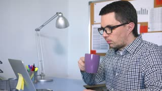A young man with a bad vision in glasses drinks hot tea from a mug behind his workplace. A man watching a movie on a laptop during a small lunch break using the Internet