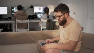 a young man with a beard on his face works in a friendly team, the person is dressed in homemade clothes and holds a laptop on his hands, he sits on the couch, behind him are computers for programming