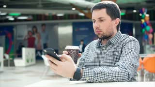 A young man with a serious appearance prints a message on his mobile phone, in his other hand is a hot coffee in a plastic glass. Person holds a smartphone in his hand, he sits in a public place.