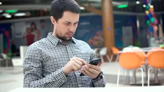 A young man with a serious look reads news on the Internet through a mobile phone, he sits at a table in the food store of a shopping center. Person touching the screen of the phone in a public place