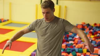 a young man with a sporty physique jumps down into inflatable squares, the person feels free falling during a jump back on toy blocks