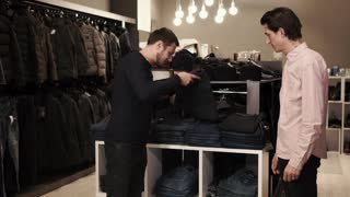 a young man with a tattoo on his neck examines black jeans for a purchase, the seller of clothing stores helps to choose the right style and size for the visitor