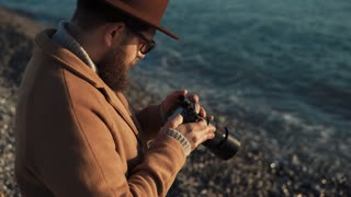 a young man with a thick beard is near the sea, the person sitting on the shore and holding a camera in his hands, he looks at the photographs