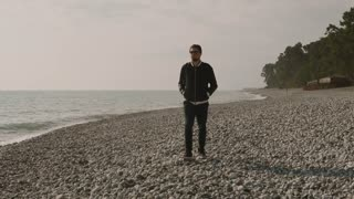 a young man with sunglasses walks along a stony beach, a gentleman is on vacation during his vacation on vacation in the summer or spring time