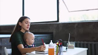 A young mother holds her daughter in her arms and works in parallel, a woman makes corrections in a notebook, the lady combines motherhood and business