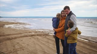 A young mother is holding a son in her arms, her husband is standing next to him and hugging an adult woman, a teenager is telling something, the family is spending a day off near the sea
