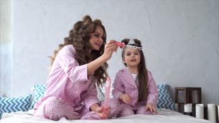 A young mother with long curly hair and her joyful daughter who is dressed in homemade pajamas are sitting on the bed in the bedroom and blowing soap bubbles.
