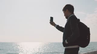 a young photographer with glasses in his eyes takes photos on the smartphone, the gentleman holds a mobile phone in his hand and is at sea on a summer day