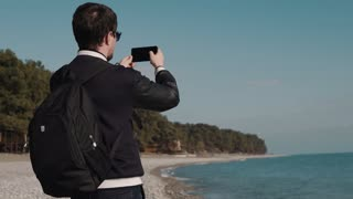 a young photographer with sunglasses on his eyes makes photos on the phone, the tourist has a briefcase on his back and stands near the sea on a summer day