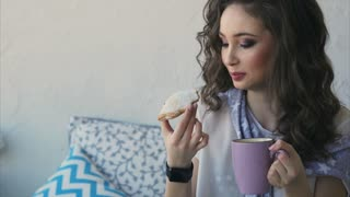 A young pretty woman takes a morning breakfast in the bedroom. She eats cookies and drinks coffee in the bed, on her hand a smart watch for checking incoming messages.