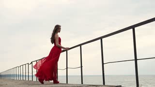 a young woman in a long scarlet dress holds onto the railing near the sea, her hair and hem of a red evening dress fluttering under the streams of wind near the sea