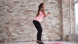 A young woman in a sports suit does the sitting, the lady performs strengthening exercises for the muscles of the legs and buttocks, she stands on the rug for yoga