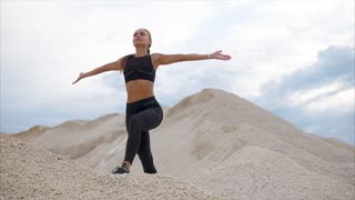 A young woman in a sports suit who does breathing exercises makes a breath and exhales in nature, the sportswoman raises her arms up and looks up at the sky