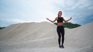 A young woman in a sports suit who does exercises on a rope for endurance is engaged in nature in the sands, a woman bounces up to strengthen the muscles