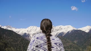 a young woman inhales clean and fresh mountain air in a nature reserve, a lady looks at the snow-capped mountains and feels their greatness