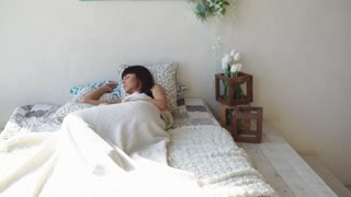 a young woman lies on the bed in her sleeping room, the lady lies her head on the pillow and looks into the distance, she recently woke up and rests