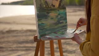 A young woman painter mixes a palette of oil paints in the palette on the easel, she is in the open air near the sea. The artist races on a canvas a landscape with a river and a mountain
