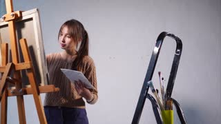 A young woman paints a picture, perhaps a landscape or a still-life in an art studio, the canvas stands on an easel, there are brushes of different thickness, the lady stands in the artistic space