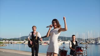 A young woman performs an energetic song under the accompaniment of musicians who play the drum set and guitar, the company is near the sea in the daytime