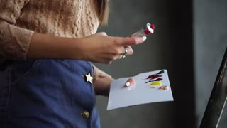 A young woman squeezes oil paint from a tube into a new palette, the artist will paint a colorful painting on canvas