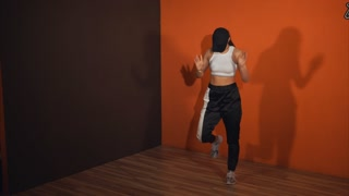 A young woman trains vigorous and free movement of the locking before starting the Battle of Hip Hop. The dancer moves her hands, stepping from place to place with her feet to the music