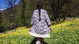 a young woman walks the hilly terrain in interesting clothes, the lady walks on the flower floor in the summer, trees and shrubs are nearby