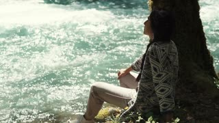 a young woman, went for a day walk to the park area, the lady sits by the river and a lonely tree, she looks at the swift flow of water