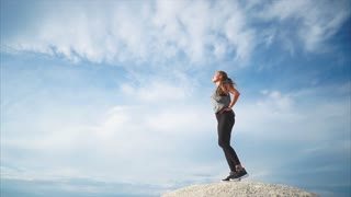 A young woman who looks like an athlete enjoys loneliness on a high mountain, from where the whole city is seen, a lady blows a cool and strong wind, her hair soars