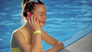 A young woman with a good figure is talking on her mobile phone in the pool, she is calling her friend to tell about the good weather on this summer day