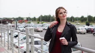 A young woman with a make-up on her eyes, who smiles gently at the distance, the lady stands next to the car parking on the street in the summer or autumn day