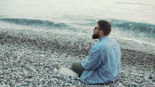 Adult bearded man with glasses is relaxing on pebble beach. He is sitting on land and looking around in evening time near river