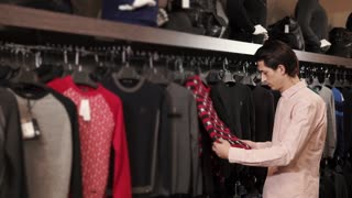 Adult handsome man is shopping in the mall alone. He is taking different clothes and looking for best.