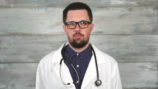 Adult male doctor with stethoscope in white coat and glasses. Concept of different professions