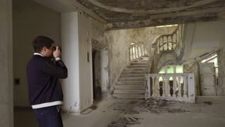 Alone tourist is taking photos inside old building. Walls and windows are dilapidated, man is walking around and using camera