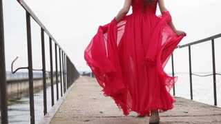 Amazing brunette woman is running across the bridge on the shore. She is wearing beautiful red dress and sandals.