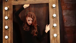 Amazing red haired model is standing within the wooden frames with bright light. She puts her hands on the top and side frames.