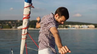 An active and outrageous man dances on a motor boat in the daytime summer, bright and energetic person move to music on a yacht during a trip on the sea
