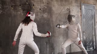 an active man and a woman are engaged in sports fencing in a protective suit, a lady and her rival each other with a sword, a gentleman wins