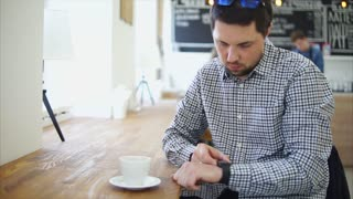 An adult and a serious person tunes a portable smart watch on his hand to receive incoming messages from the phone to the bracelet, the man sits in a small cafe