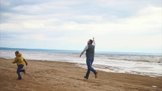 An adult dad and his young son run along the coastline near the sea with a kite in their hand, a man and a boy happily spend time together on a day off