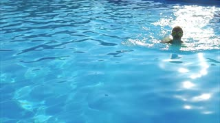 An adult girl in round sunglasses and a swimsuit swims in the pool on a hot summer day, she enjoys cool blue water, where the sun is reflected