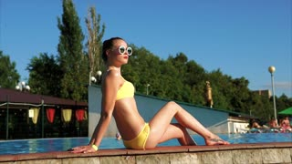 An adult girl with a good figure who wore a bright swimming swimsuit sunbathing in the sun near the swimming pool, sunglasses protect the eyes from the summer sun