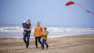 An adult man carries a small child in his arms, his son plays with a kite that develops in the air, mom goes happy along the beach along the sea, on the street cold weather