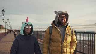 an adult man in sunglasses and his wife who is dressed in a unicorn suit are walking along the street on a sunny day, the couple in winter jackets are walking with a good mood