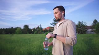 An adult man wearing sport suit holds a plastic bottle in his hand, a bearded person in a sports suit drinks water drinks in the summer in a park