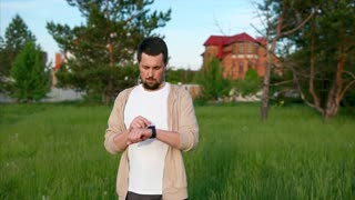 An adult man with smart watch on his hands checks how many kilometers and for what time he ran in the summer time in the park, people looking at the display
