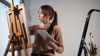 An adult teenager holds in his hand a palette with oil paints, a canvas on which a lady creates a picture stands on an easel in an art studio